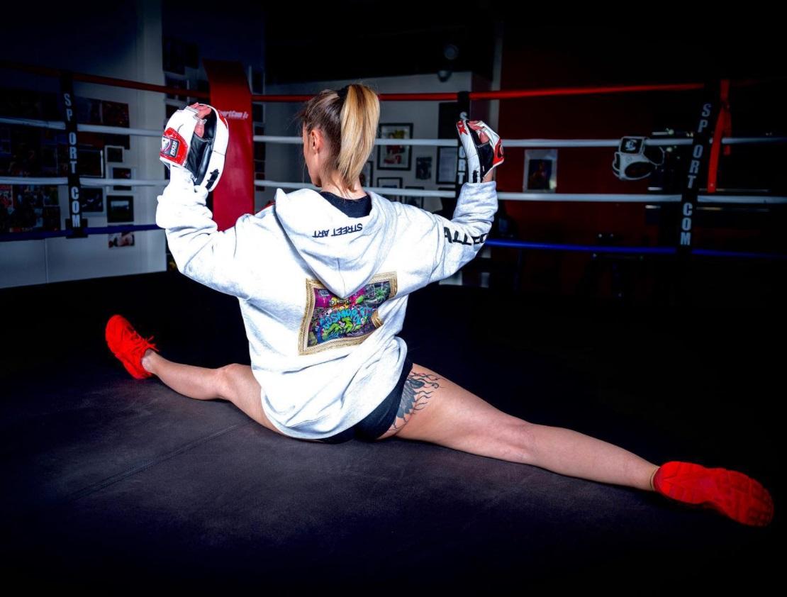 Femme faisant le grand écart sur un ring de boxe