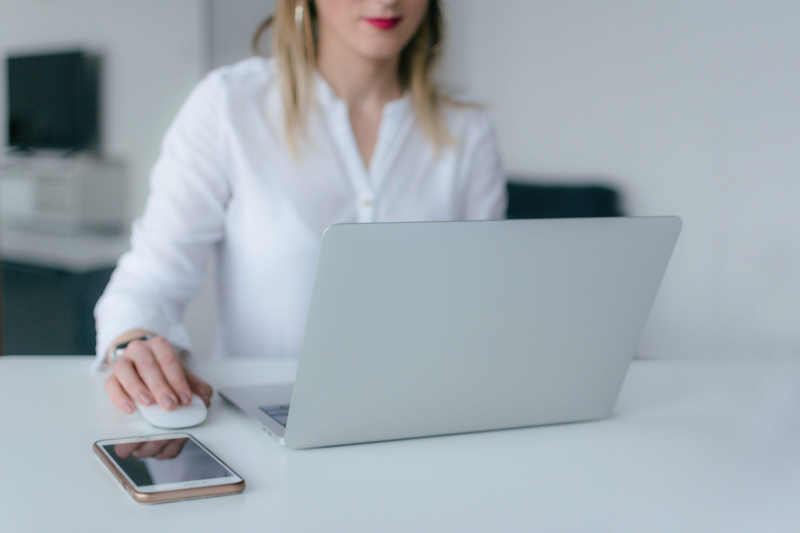femme blonde chemise blanche utilise ordinateur portable avec souris bluetooth