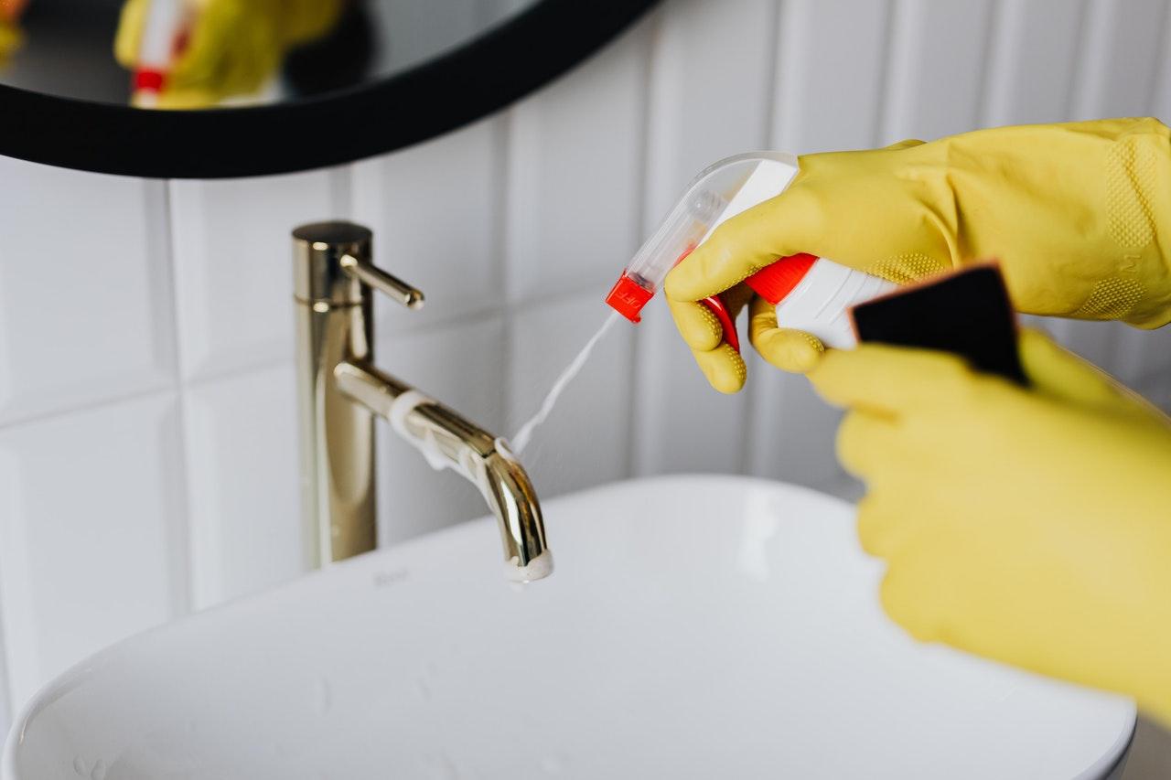 gants jaune éponge nettoyer acide chlorhydrique robinet de lavabo dans salle de bain